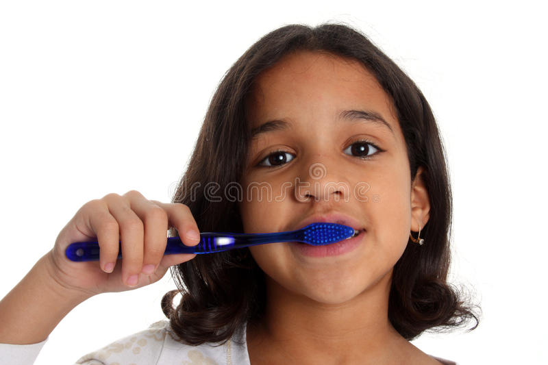 Girl Brushing Teeth. Young girl with brown hair brushing teeth on white background stock photo