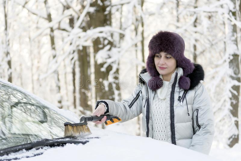 The girl is brushing the windshield of the car from the snow. Winter, day stock photos
