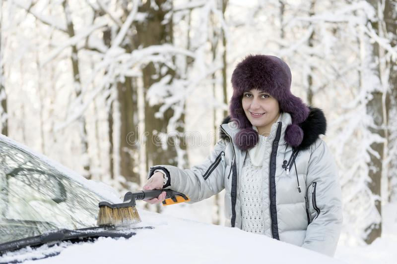 The girl is brushing the windshield of the car from the snow. Winter, day royalty free stock photo