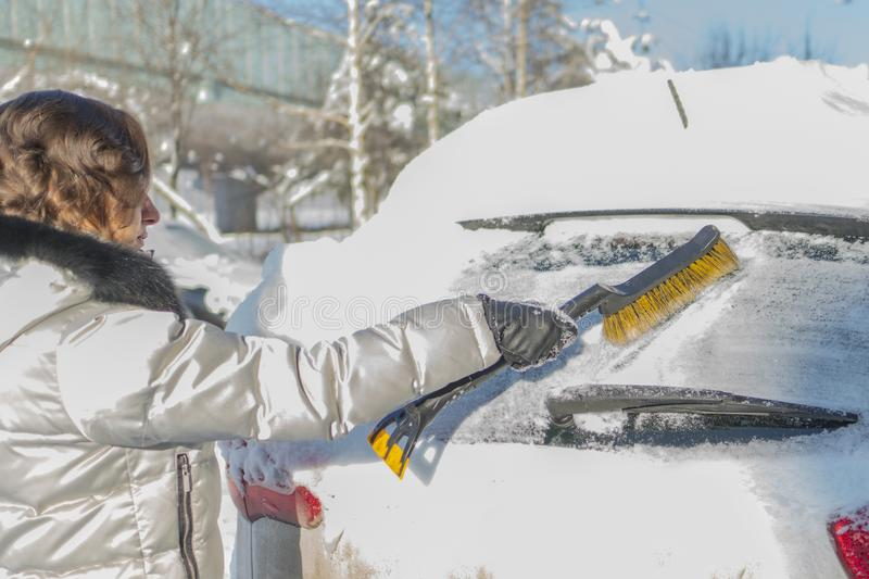 The girl is brushing the windshield of the car from the snow. Wi. Nter, day stock images