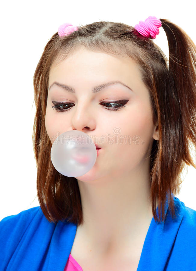 Girl with bubble. Beautiful young lady blowing big bubble gum on white background royalty free stock photo