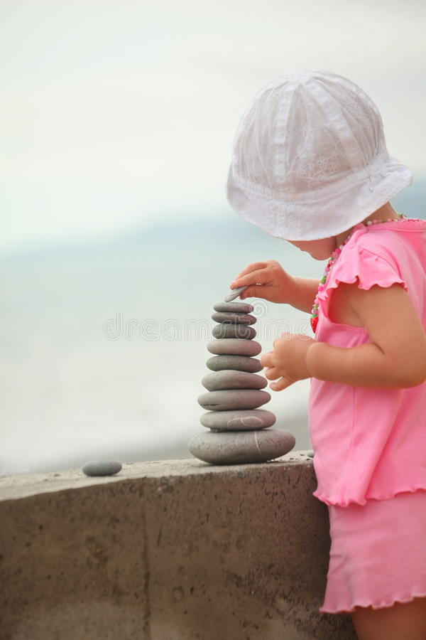 Girl is building a construction from pebble stones stock images