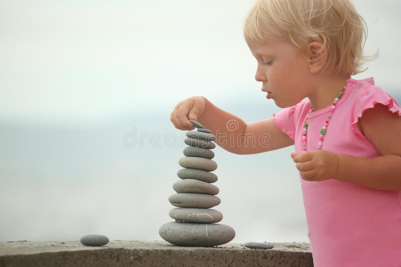 Girl is building a construction from pebble stones royalty free stock photo
