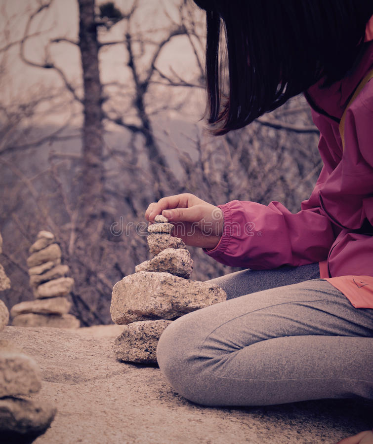 Girl Building a stone tower stock photos