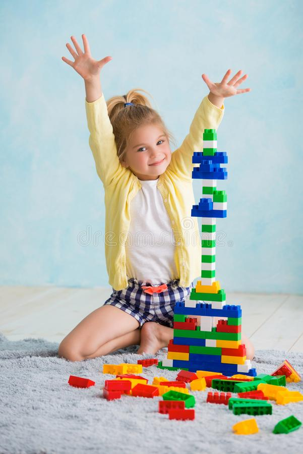 The girl built a tower of cubes. The joy of games stock photo