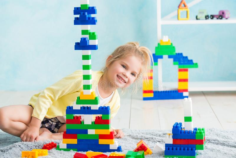 The girl built a tower of cubes. The joy of games royalty free stock image