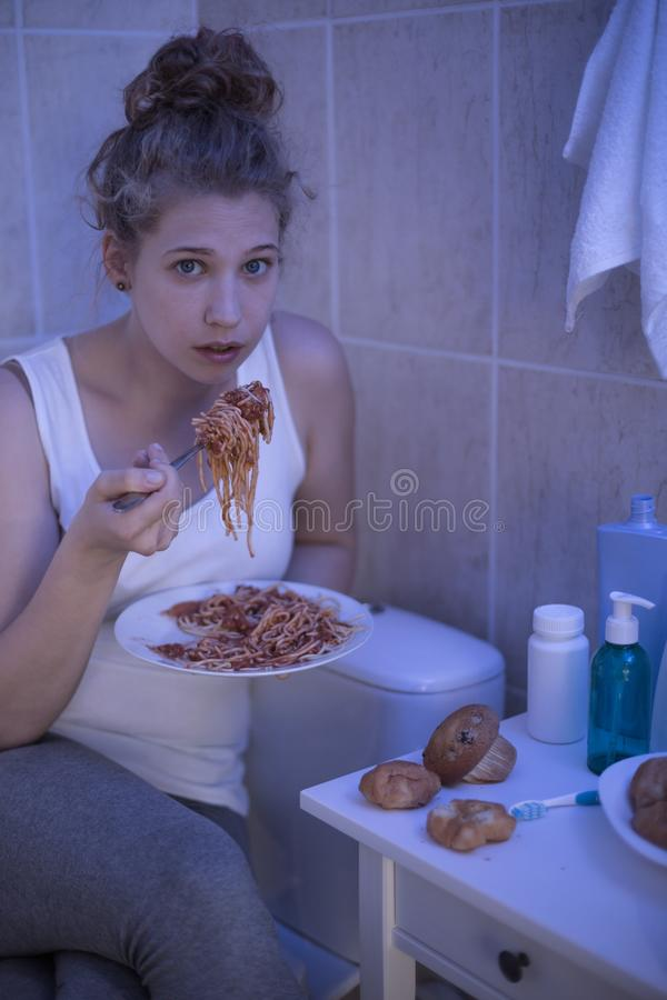 Girl and bulimia. Girl with bulimia is eating spaghetti stock photography