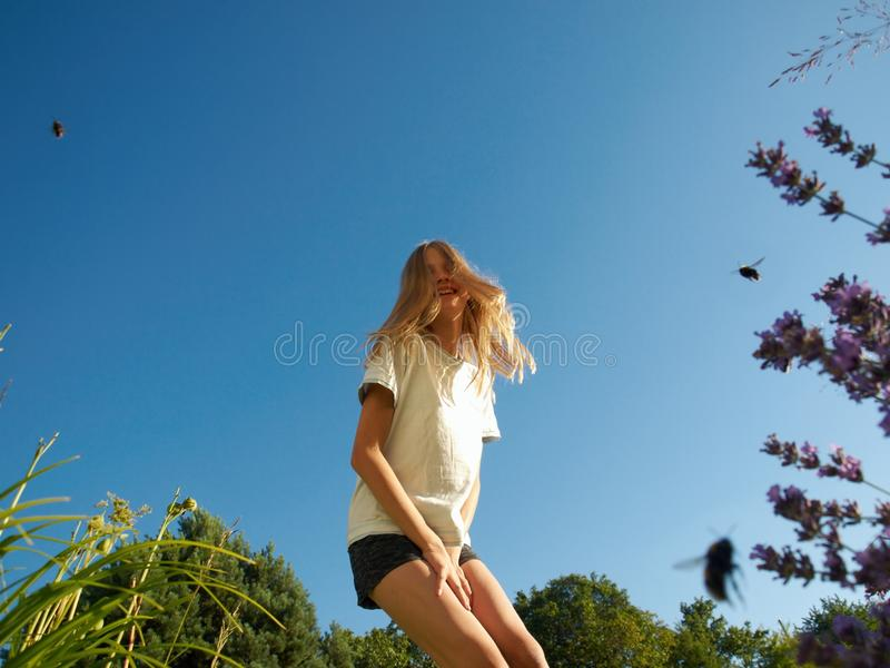 Girl and bumblebees. Blonde girl from below on the garden with bumblebees, lavender and blue sky stock photo