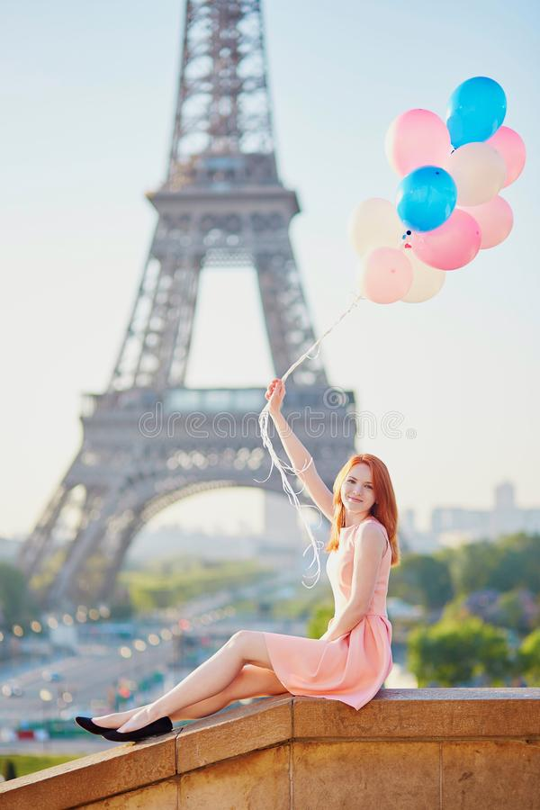 Girl with bunch of balloons in front of the Eiffel tower in Paris royalty free stock photos