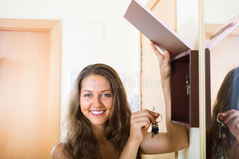 Girl with bunch of keys. Happy smiling girl with bunch of keys staying near house-keeper stock image