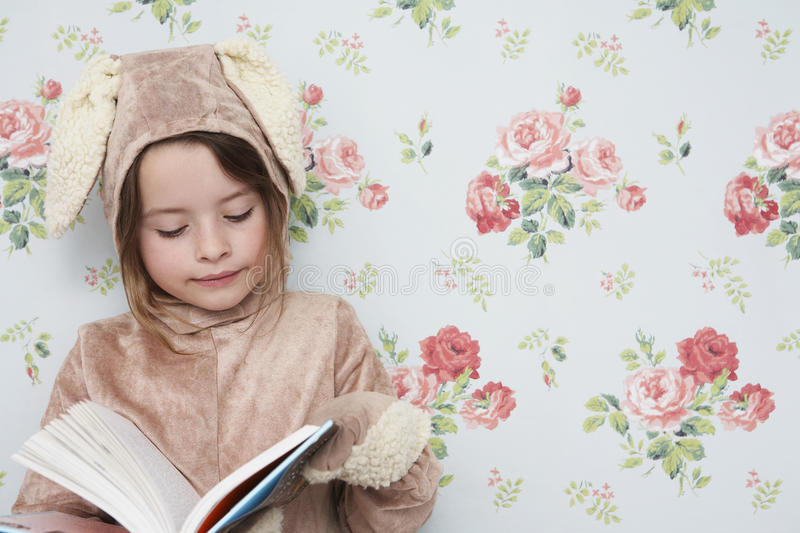 Girl In Bunny Costume Reading Against Wallpaper. Young girl in bunny costume reading book against wallpaper with floral pattern royalty free stock photo