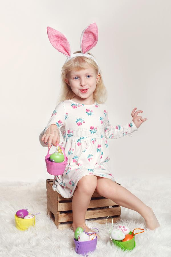Girl with bunny ears and toys eggs celebrating Easter holiday stock photo
