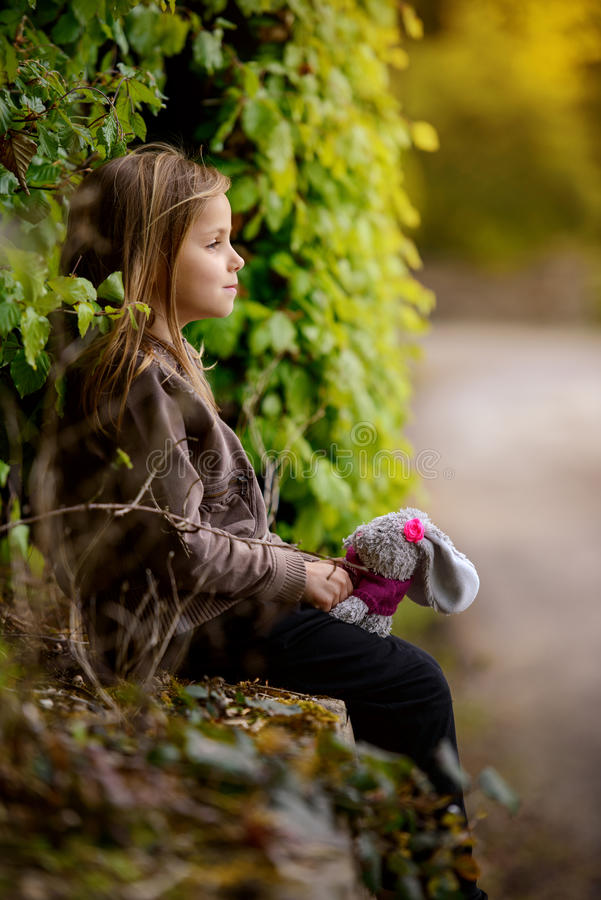 Girl with bunny. Little girl sitting with bunny royalty free stock images