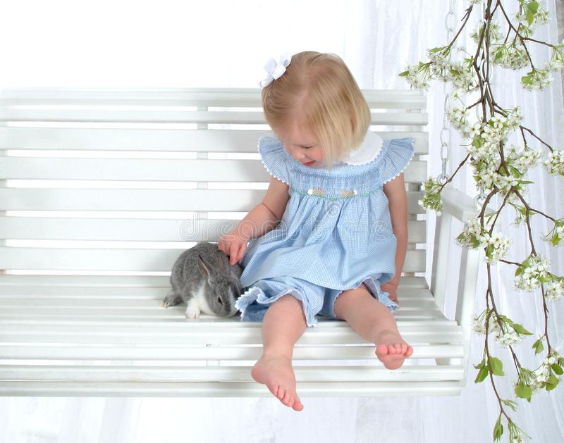 Girl and Bunny on Swing stock images
