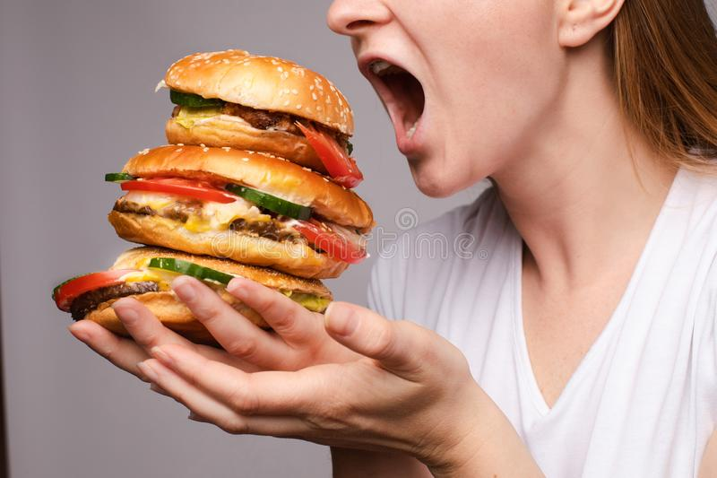 The woman opened her mouth to eat a hamburger. Girl with a burger in his hands opened her mouse to eat a big portion of hamburger stock photos