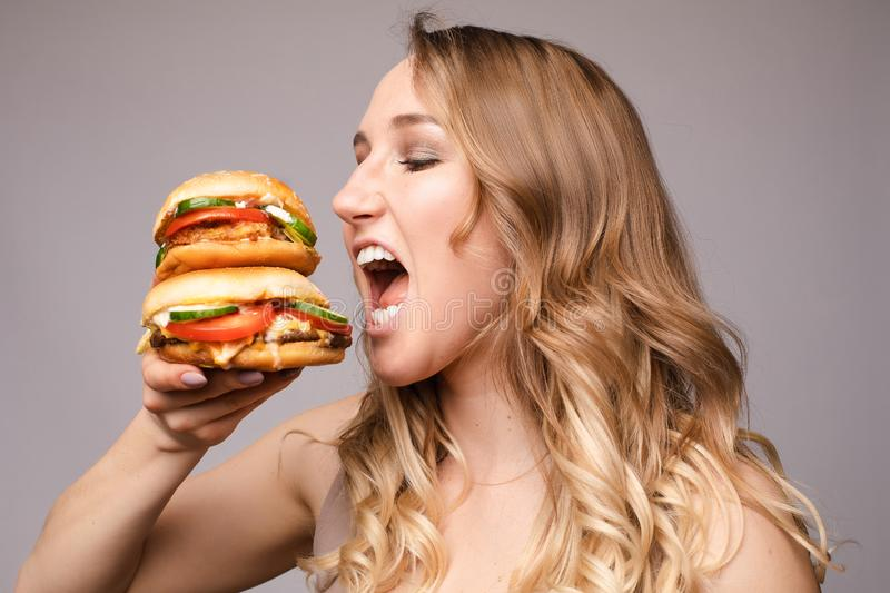 The woman opened her mouth to eat a hamburger. Girl with a burger in his hands opened her mouse to eat a big portion of hamburger stock image