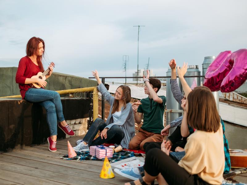 Girl busker play ukulele music art leisure enjoy. Girl busker playing ukulele at a rooftop. Artistic musician lifestyle. Teenagers leisure. Friends enjoy music royalty free stock image