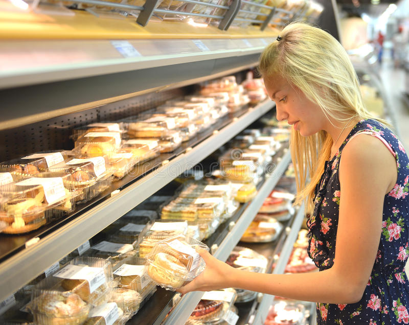 Girl buying cakes in supermarket. Side view of young blond girl buying fresh cakes in supermarket royalty free stock photos