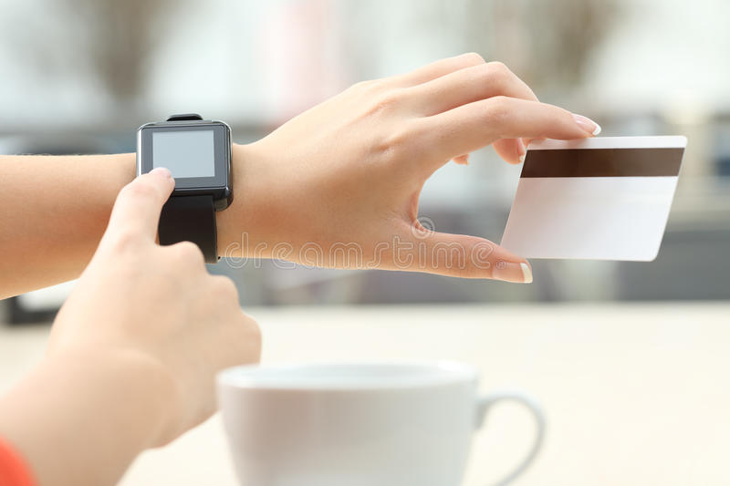 Girl buying online with credit card and smartwatch. Close up of a girl hands buying on line with a credit card and a modern generic smart watch in a bar terrace royalty free stock photos