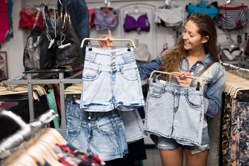 Girl buying shorts stock image