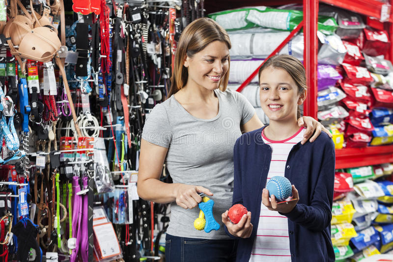 Girl Buying Toys With Mother In Pet Store. Portrait of happy girl buying toys with mother in pet store royalty free stock photo