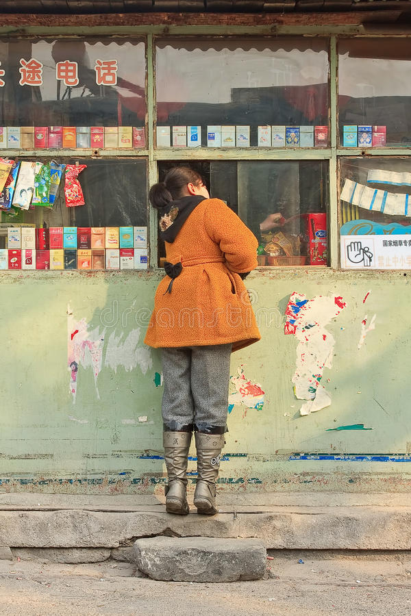 Girl buys candy in a neighborhood shop, Beijing, China royalty free stock image