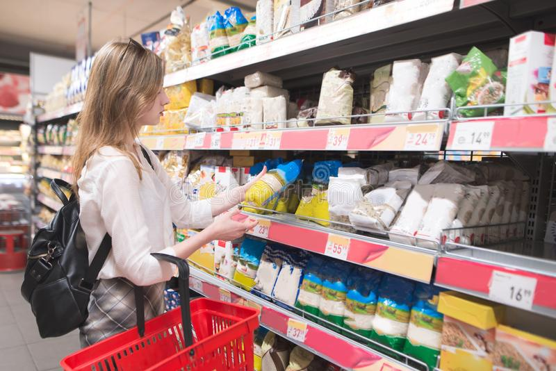Girl buys groats in the grocery store. Shopping in a supermarket stock images