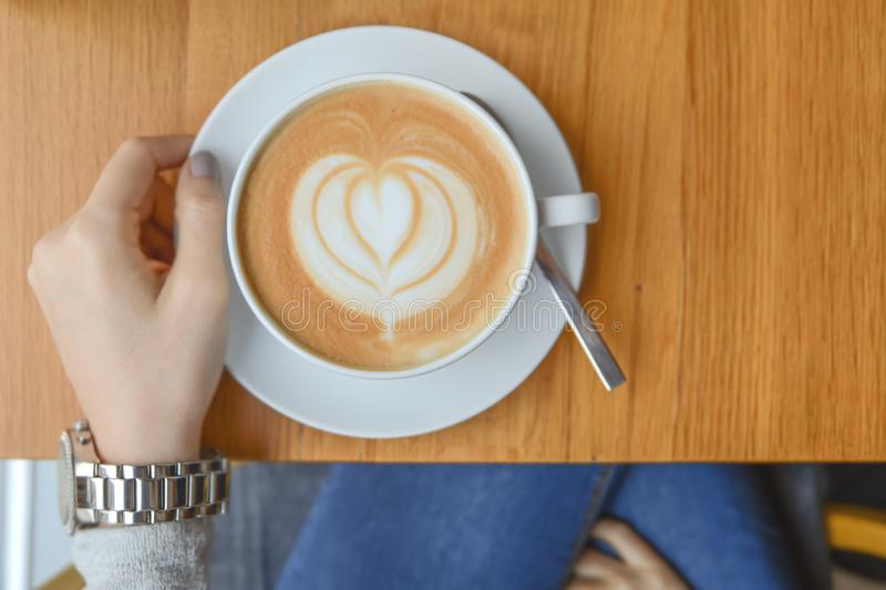 Girl in cafeteria with big cup cafe latte on table for morning. Break stock image