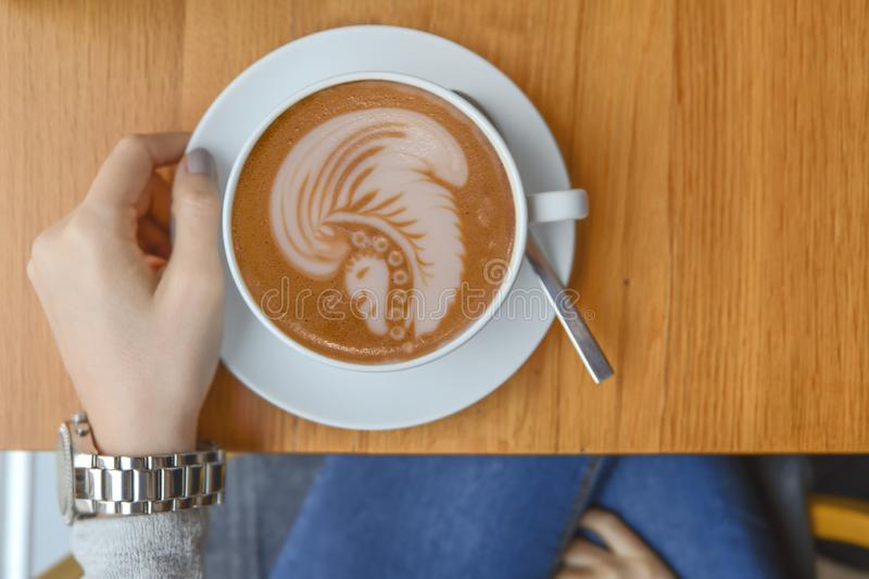 Girl in cafeteria with big cup of mocha and indian latte art on table. For morning break royalty free stock images