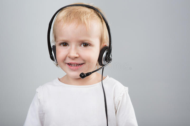 Girl call center. Cute kid girl talking to customers as a consultant call center using headset. Girl is working as an operator at helpline. Gray background royalty free stock photography