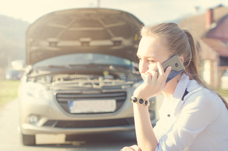 Girl calling. Broken car on a background. Woman sit on a wheel. young woman repair a car. Natural background. Car accide. Broken car on a background. Woman sit stock photography