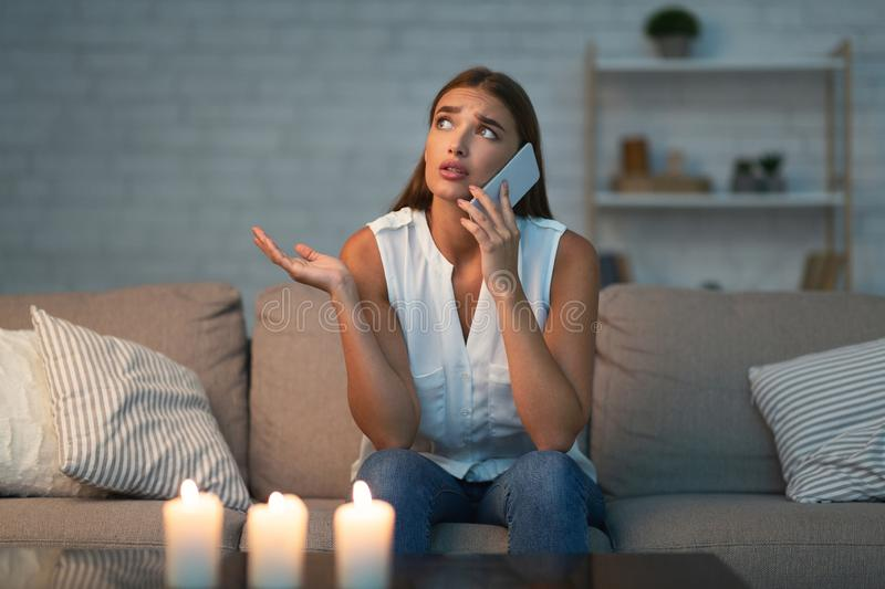 Girl Calling Electrician Service Sitting On Couch In Dark Room royalty free stock photos