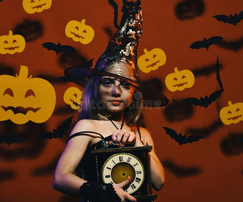 Girl with calm face on bloody red background. With bats and pumpkins decor. Kid in spooky witches costume holds old clock. Halloween party and decorations royalty free stock image