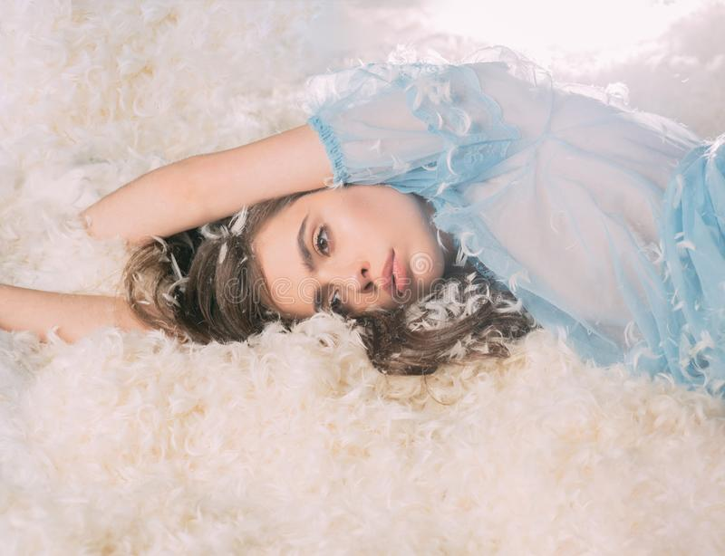 Girl on calm face lay on bed covered with feathers and fluff. Airiness concept. Lady in transparent blue nightie lay on. Bed in heap of feathers. Woman with stock photo