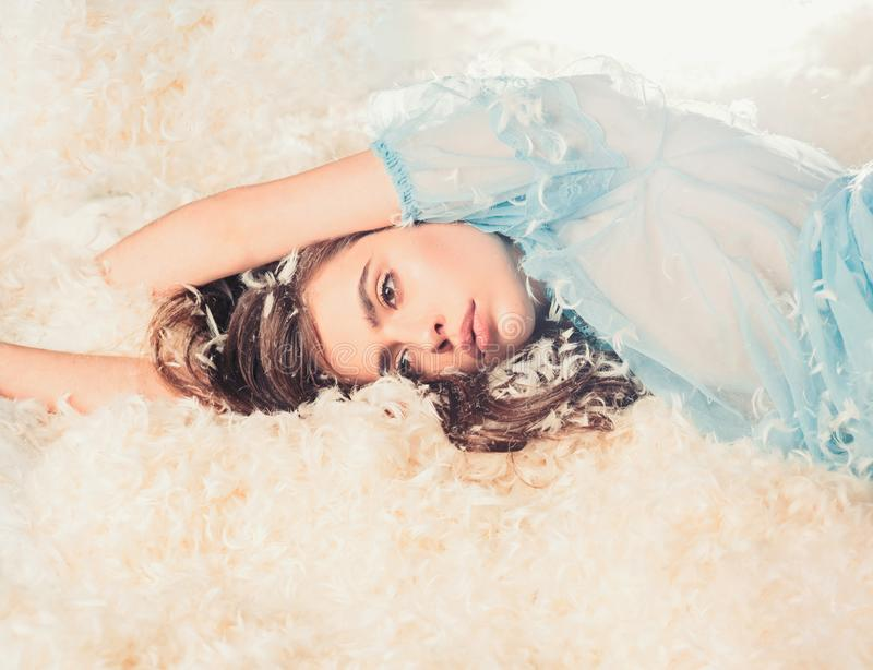 Girl on calm face lay on bed covered with feathers and fluff. Airiness concept. Lady in transparent blue nightie lay on. Bed in heap of feathers. Woman with royalty free stock images