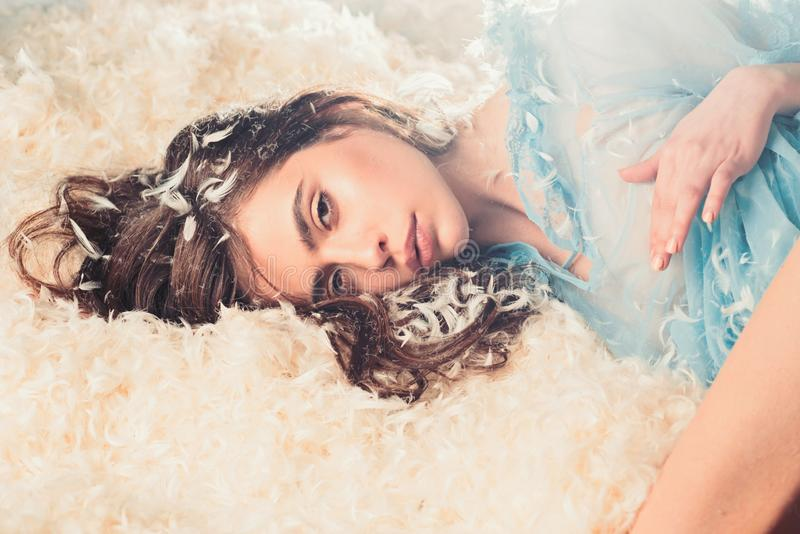 Girl on calm face lay on bed covered with feathers and fluff. Airiness concept. Woman with long hair in tender pajama. Relaxing. Lady in transparent blue royalty free stock photos