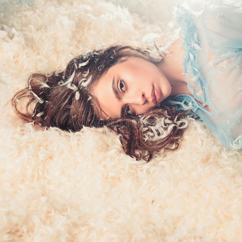 Girl on calm face lay on bed covered with feathers and fluff. Woman with long hair in tender pajama relaxing. Lady in. Transparent blue nightie lay on bed in royalty free stock photo