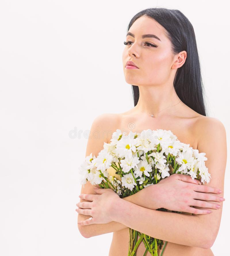 Girl on calm face naked holds chamomile flowers in front of breasts. Woman with smooth healthy skin looks attractive royalty free stock photography