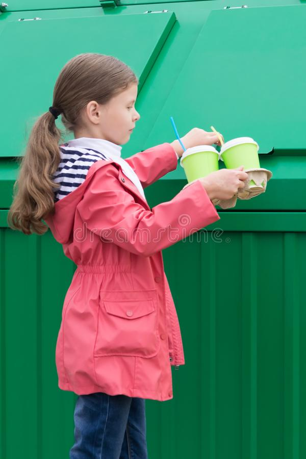 Girl came to throw paper glasses in the trash tank. Girl came to throw paper glasses in  the trash tank stock photography