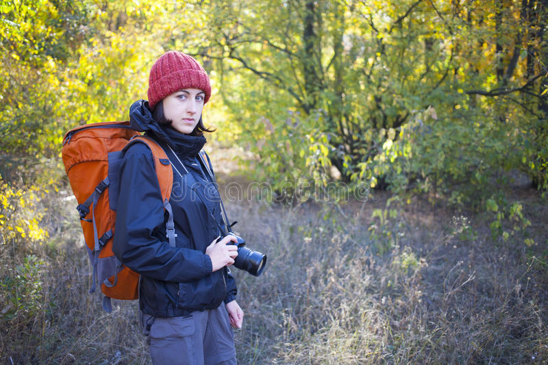 A girl with a camera and a backpack. The girl with the camera and the backpack goes on the trail in a beautiful forest royalty free stock photos