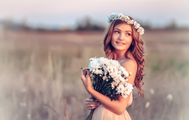 Girl in a camomile wreath. Beautiful girl in a camomile wreath royalty free stock photography