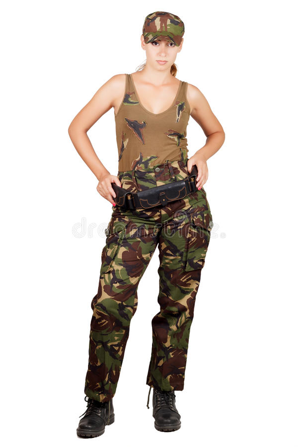 Girl in camouflage with a cartridge belt, standing with hands on hips. Isolated on white background royalty free stock photo