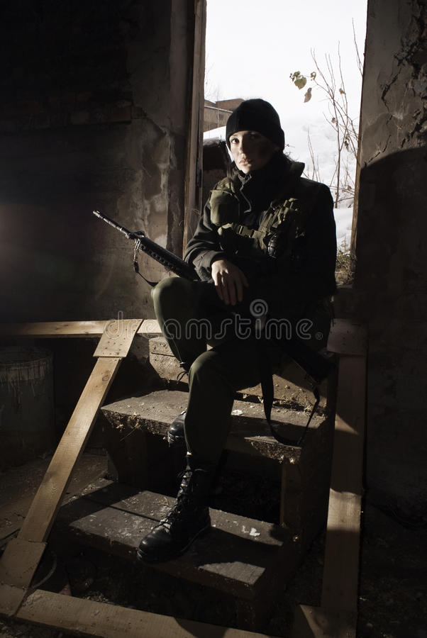 Girl in a camouflage with the gun in hands stock images