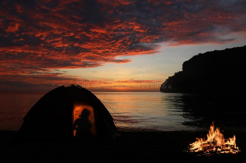 Girl camping alone with campfire on the beach,Red sky sunset background royalty free stock photography