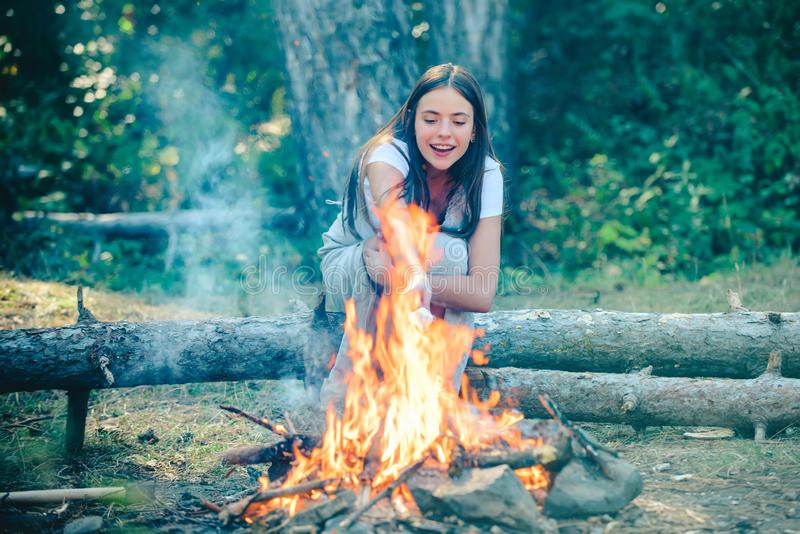 Girl camping with marshmallows over a camp fire. Girl enjoying picnic in the forest. Vacation weekend picnic camping and stock photos