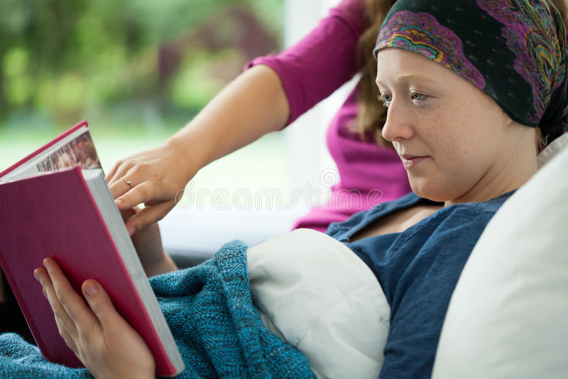 Girl with cancer holding photo album stock photography