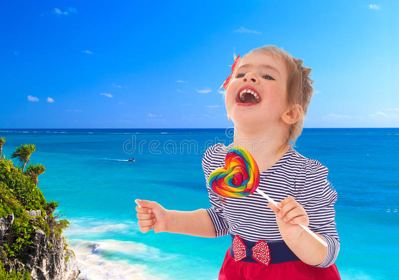 Girl with candy on a background of the sea. royalty free stock photo