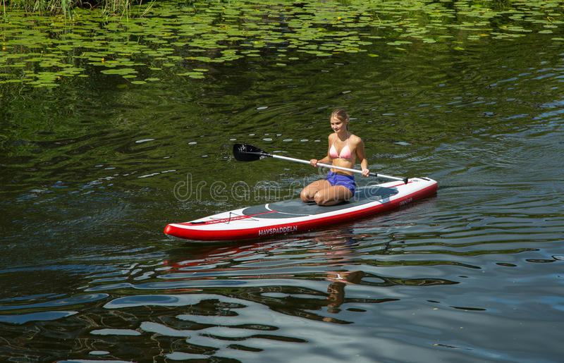Girl in canoe paddling on a canal in the city stock image