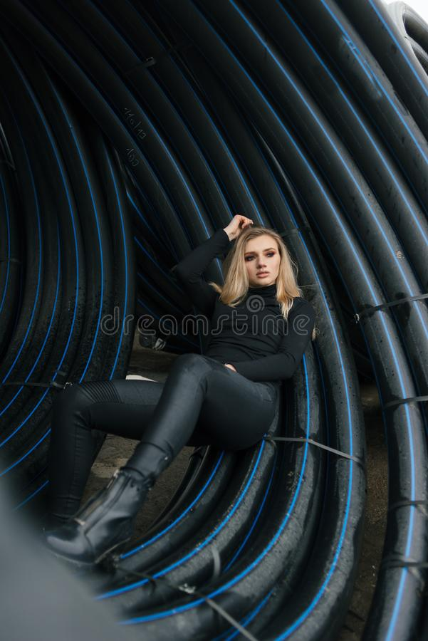 A girl in a canopy of pipes looking out into the distance stock photos