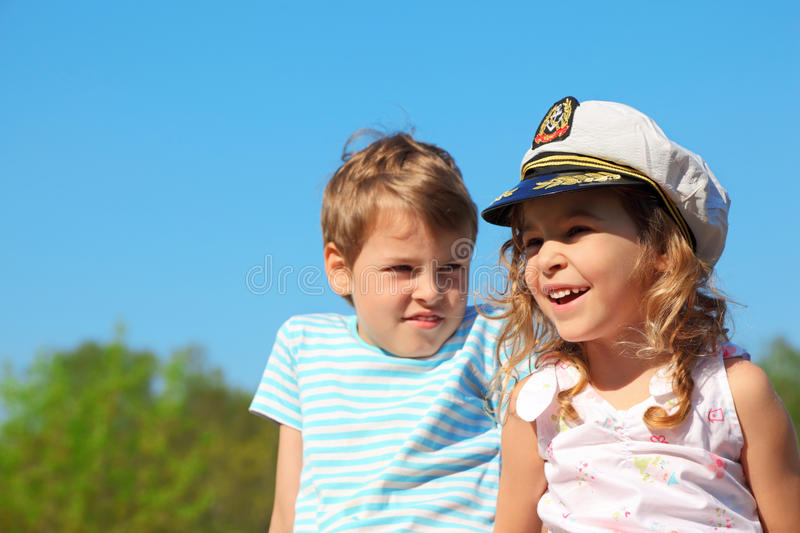 Girl with captain cap and boy at sunny day